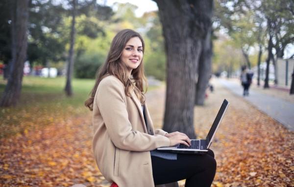 Photo: Pexels. Smilende kvinnelig student med laptop i et høstlig utemiljø