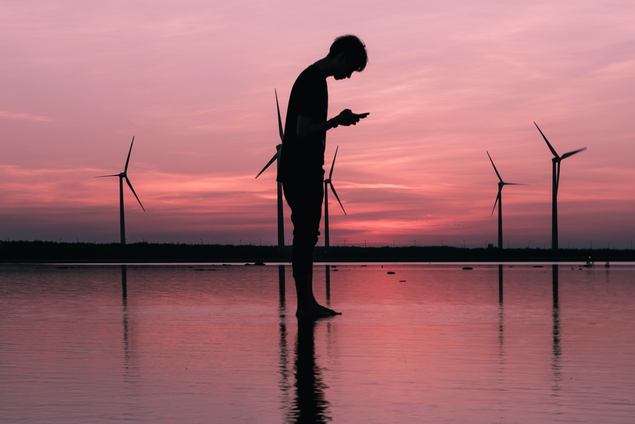 Silhouette photo of man standing while using smart phone in front og wind turbins and a pink sunset. Credits: Unsplash.com/@themodernaffliction