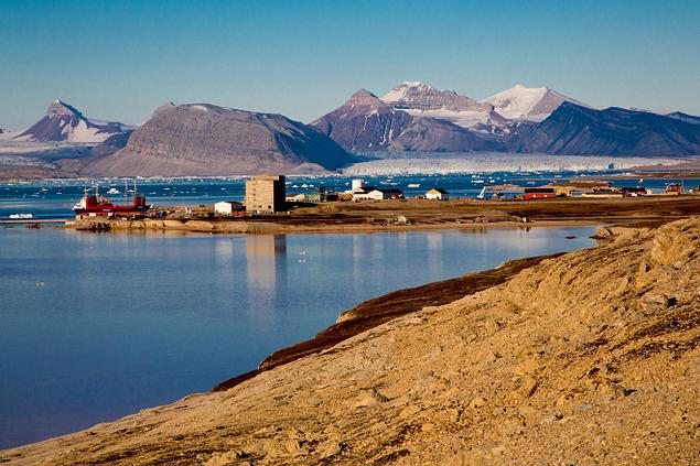 Utsikt over Ny Ålesund, Svalbard. Storslåtte fjell og blå fjord med noen hus på et nes, samt et stort skip