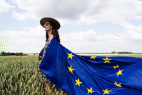Bilde av kvinne i kornåker med hatt, solbriller og et stort EU-flagg drapert over skuldrene. Foto: Eu-kommisjonen
