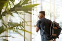FNI søker masterstudent til stilling som vitenskapelig assistent. Mann går ut av glassdør. Foto:  linkedin sales navigator on unsplash